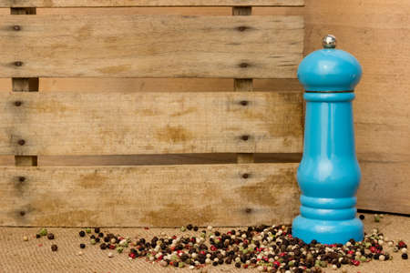 Pepper and pepper mill over wooden background
