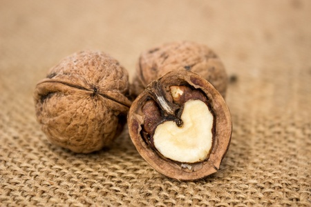 cracked walnuts on rustic fabric Stock Photo