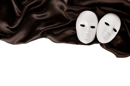 White masks and black silk fabric, isolated on white  Stock Photo