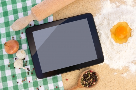 Examine digital recipe on tablet at kitchen to prepare the lunch