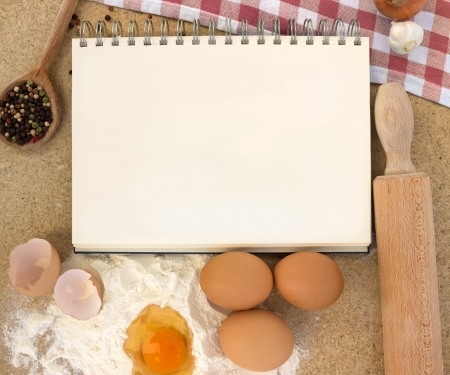 recipe book with flour, eggs and rolling-pin on a wooden table
