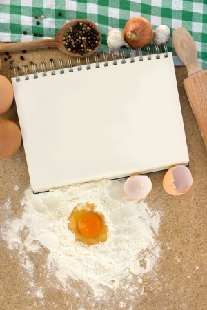flour for the dough with blank notebook for recipes
