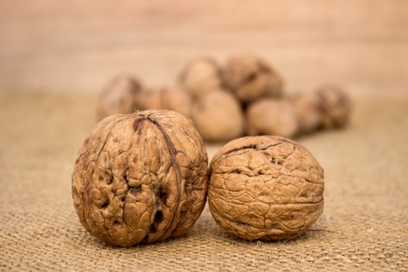 Close up of two walnuts with pile of walnuts in background