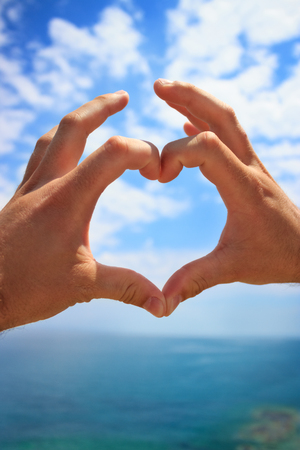 hands make heart sign over beautiful sky Stock Photo