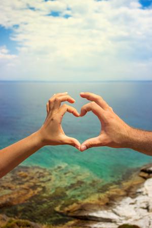 pareja cogidos de la muestra del coraz�n, el amor y el mar