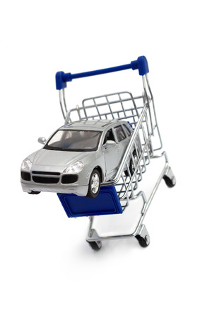 A car in a shopping cart isolated on white photo