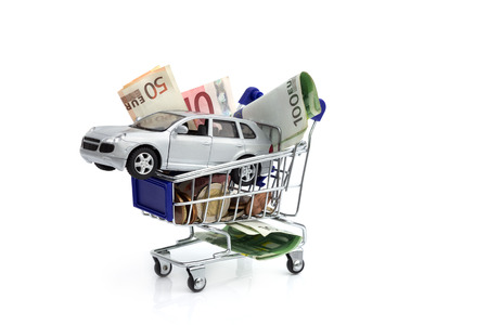 car retailer: shopping cart with money and car, concept - buy and save