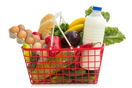 白い背景の上分離された食料品が付いているバスケットをショッピング