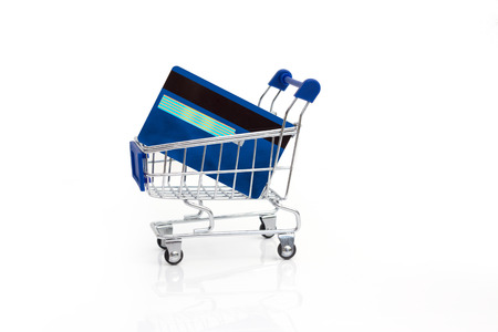 online trading:  Shopping cart and credit cards on laptop, e-commerce.