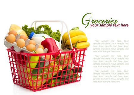 Cesta de la compra con alimentos, aislados sobre fondo blanco Foto de archivo