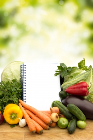Fresh vegetables with notes on wooden table on green background