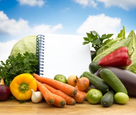 Diferentes verduras frescas con papel vac�o, el concepto de dieta Foto de archivo