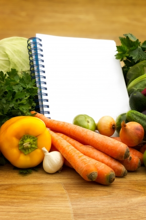 Fresh vegetables and paper for notes, on wooden background Stock Photo
