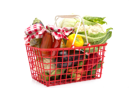 Shopping basket with fresh vegetables and vegetables in jars