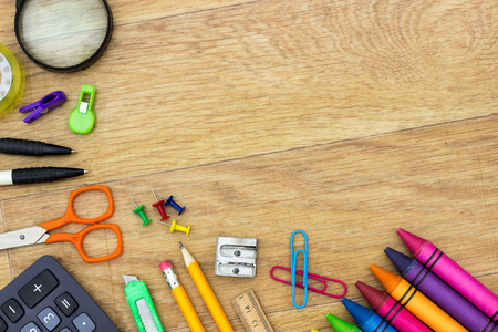Assortment of various school items on wooden background