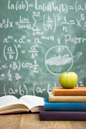back to school concept - white chalk handwriting on blackboard, stack of books and apple Foto de archivo