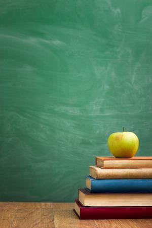 chalkboard: livres scolaires à la pomme sur le bureau plus école verte board background