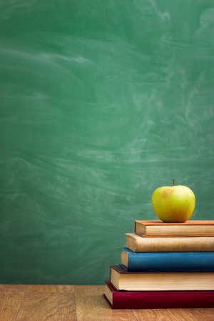 School books with apple on desk over green  school board background Standard-Bild - 33271646