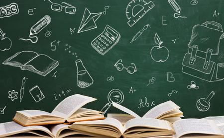 Libros escolares abiertos con bocetos escritos en la mesa de la escuela