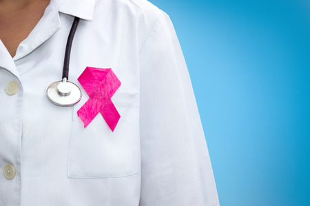 healthcare and medicine concept - female doctor with pink breast cancer awareness ribbon Standard-Bild