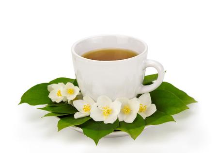 Taza de t� con flores de jazm�n en la placa Foto de archivo