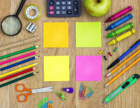 Colorful sticky notes with school items over wooden background photo