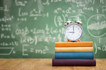 school books with alarm clock on green school board background Foto de archivo