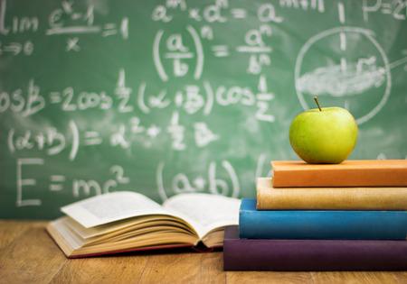 Libros de texto con la manzana en el escritorio sobre el fondo de la junta escolar verde