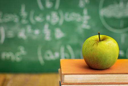 Apple on  school books over green  blackboard