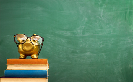 piggy bank with glasses on books, education concept Banque d'images