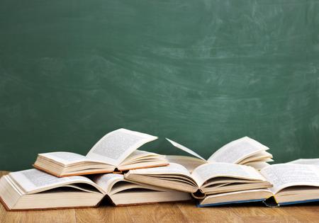 Open books front empty green blackboard
