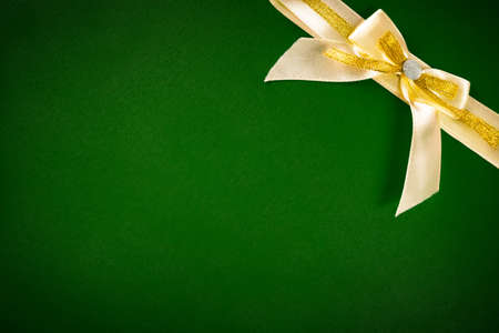 Holiday Background, greeting card, gold bow on a green background