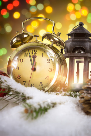 New Years at midnight - Old clock with snow and holiday lights photo