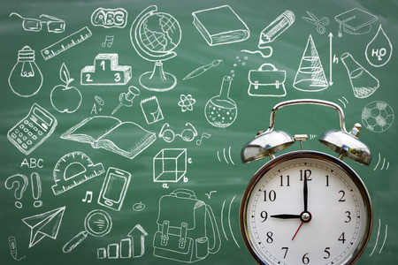 late: Alarm clock over blackboard with sketching school supplies Stock Photo