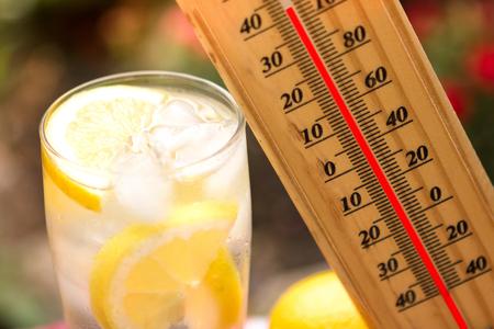 sediento: cálido día de verano, el termómetro al lado limonada fría muestra la temperatura alta