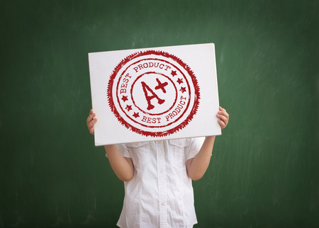 signet: student shows his grade, holding a paper with a stamp A plus grade overhead
