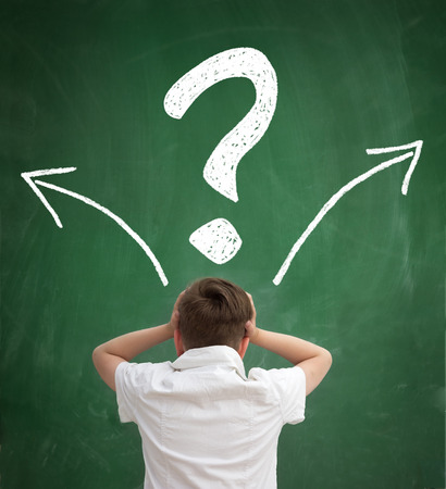 schoolboy thinking with question marks overhead, back view Banque d'images