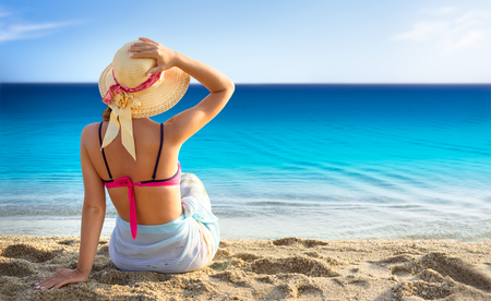 Beach vacation, young woman in sunhat and bikini sitting with her arm raised to her head enjoying looking view of beach ocean on hot summer day.