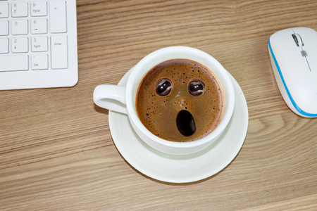 coffee cup with astonished expression in  in cream coffee, funny concept Фото со стока