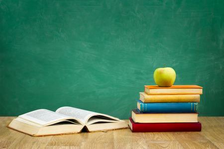 Stapel der Bücher mit einem Buch offen auf leeren grünen Schulbehörde Hintergrund