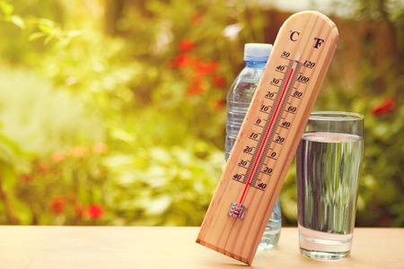 Thermometer on summer day showing high temperature near 45 degrees