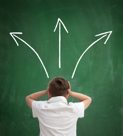 schoolboy make important decisions concerning their schooling, child looking in tree arrows on blackboard Stock Photo
