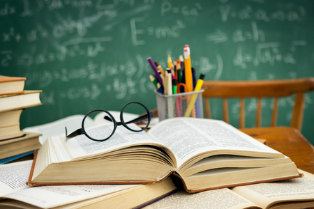 Desk full of open books over green blackboard