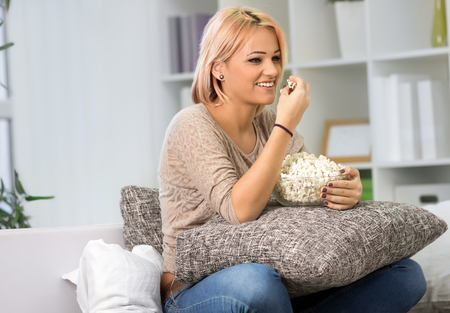mujeres fashion: Attractive young girl eats popcorns and watch television Foto de archivo