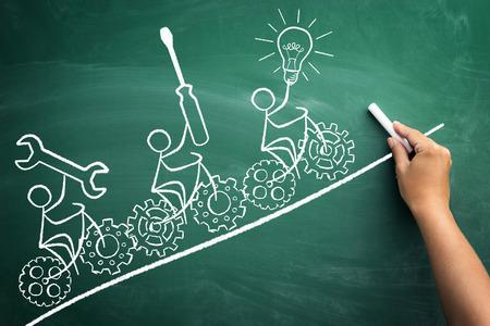stickmen: symbolic representation of teamwork with a drawn stickmen who ride their bikes on blackboard Stock Photo