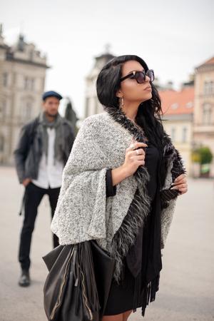 Chica atractiva con gafas caminando en la calle y no prestar atención a chico detrás de ella Foto de archivo