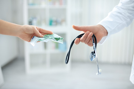 corruptible: Young corrupt doctor taking bribe from patient Stock Photo