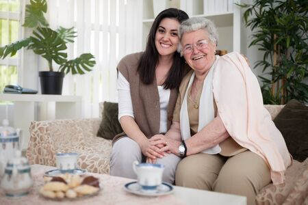 vecchiaia: Granddaughter and grandma embraced and smiling Archivio Fotografico