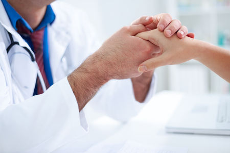 doctoring: medical doctor holing patients hands and comforting her Stock Photo
