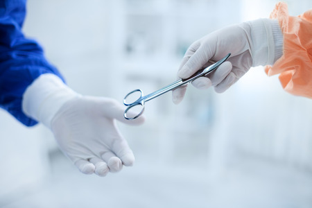 by pass surgery: Assistant gives scissors for operation to surgeon Stock Photo